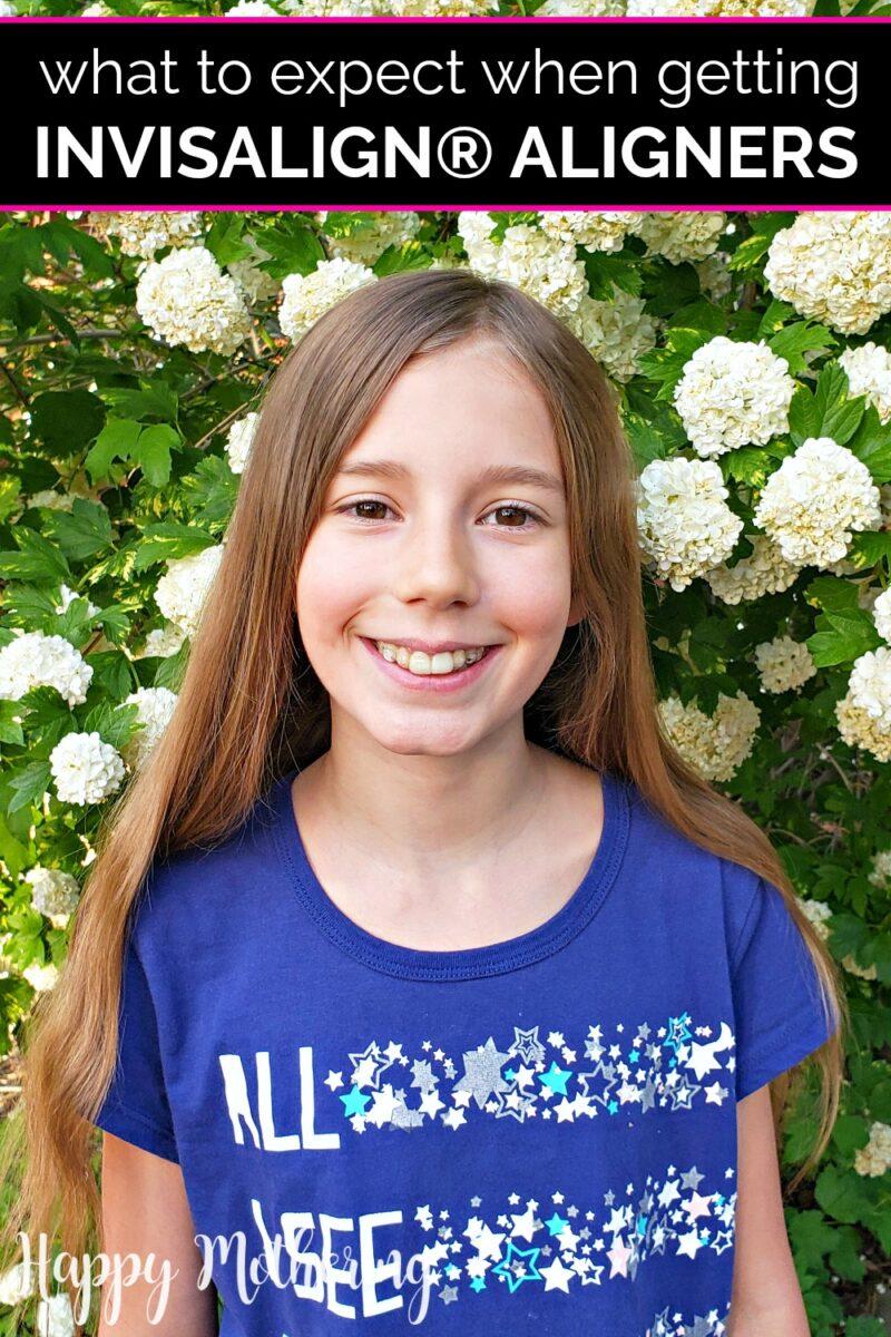 Zoe smiling in front of hydrangea bush