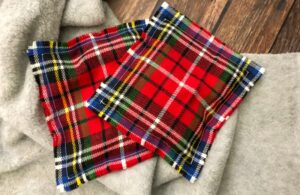 Two homemade reusable hand warmers in red plaid flannel on a sweater