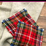 Two red flannel reusable hand warmers with a tan scarf on a wood table