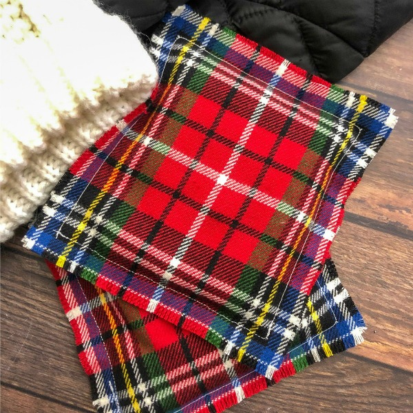 Red plaid flannel hand warmers on a table with a beanie and jacket