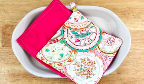 One pink and one paisley DIY pot holder in a casserole dish on a counter