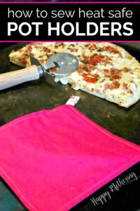 Pink pot holder on stove next to cut pizza