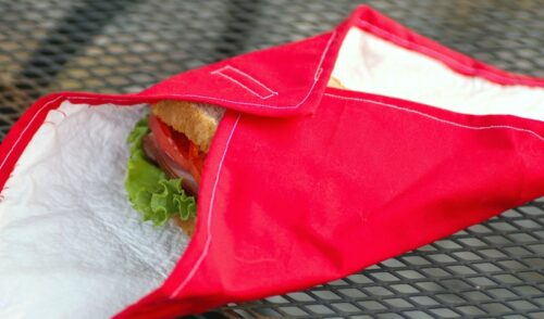 Homemade red reusable sandwich wrap partially opened with a sandwich exposed on a metal table