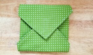 Completed reusable sandwich wrap in green and white polkda dot fabric on a light wood table