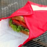 Red DIY reusable sandwich wrap on a metal table