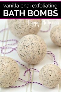 Five vanilla chai tea exfoliating bath bombs on a white wood table with purple and white baker's twine