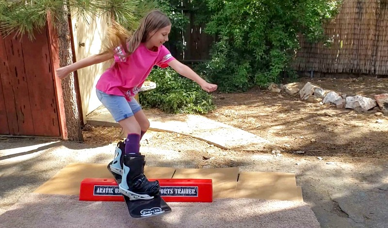 Zoë practicing snowboarding on the active trainer in the backyard