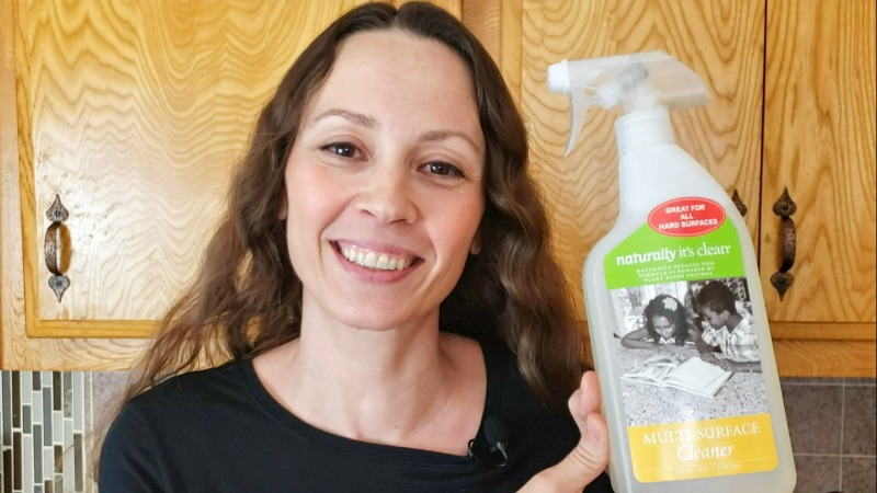 Chrystal holding a bottle of Naturally It's Clean Multi-Surface Cleaner