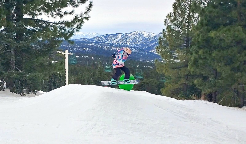 Going over a jump on a snowboard