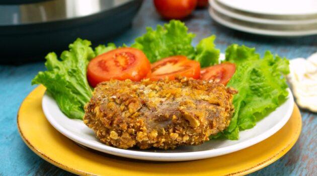 Crispy coated pork chop made in the air fryer on a white plate with tomato and lettuce