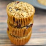 Three blueberry baked oatmeal muffins stacked in front of a muffin pan