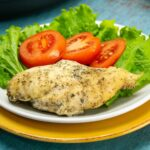 Seasoned chicken breast on a white plate with tomatoes and lettuce that was cooked in an Instant Pot pressure cooker