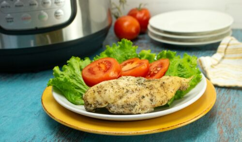 Chicken breast, lettuce and tomato on a white plate on a blue wood counter in front of an Instant Pot