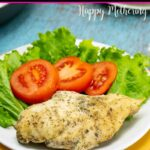 Juicy seasoned chicken breast on a plate with tomato and lettuce