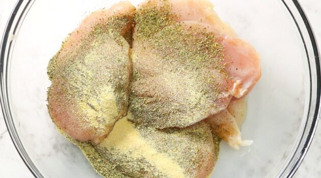 Chicken breasts and seasoning in a glass mixing bowl