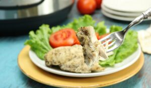 A bite of chicken breast on a fork in front of a dinner plate