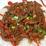 Close up of Mongolian Beef and Broccoli over white rice and topped with Sriracha that was made in an Instant Pot