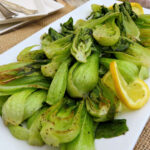 Close up of two boy choy halves roasted on a pan with more in the background