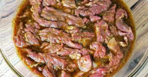 Marinated skirt steak in mixing bowl.