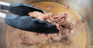 Cooked carne asada being removed from Instant Pot with tongs.