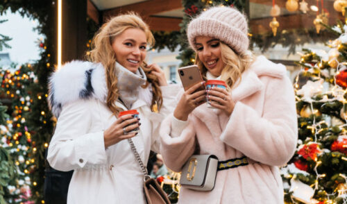 Two sisters shopping during Christmas time, talking and looking at a phone