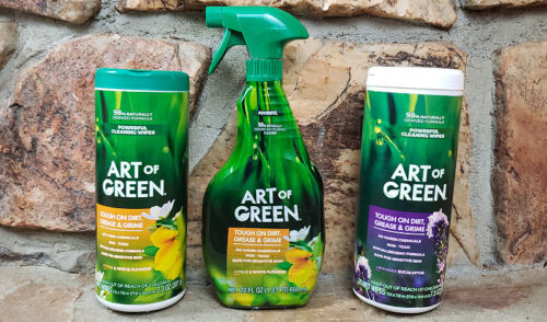 Two canisters of Art of Green cleaning wipes and one spray bottle of cleaner on the fireplace