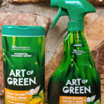 One canister of cleaning wipes and one spray cleaner by Art of Green on fireplace background