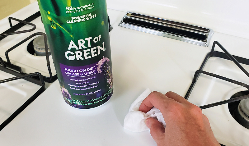 Art of Green cleaning wipes being used to clean a white stove