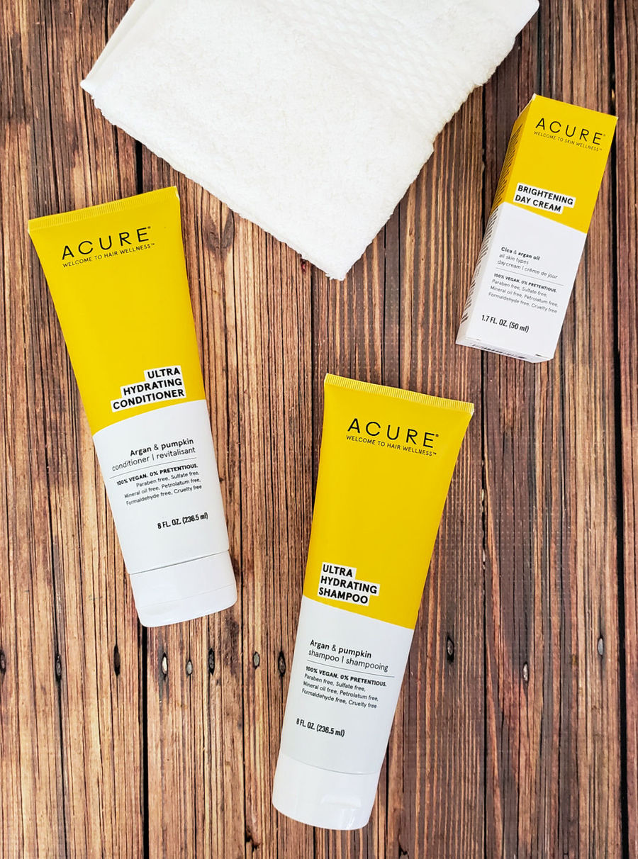 Acure shampoo, conditioner and brightening face cream on a wood table with a white wash cloth.