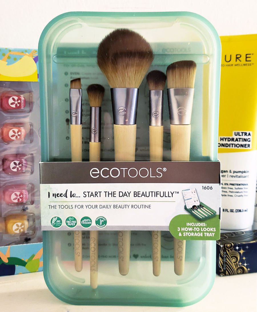 Ecotools Makeup Brushes in clear green case in front of personal care product bottles.