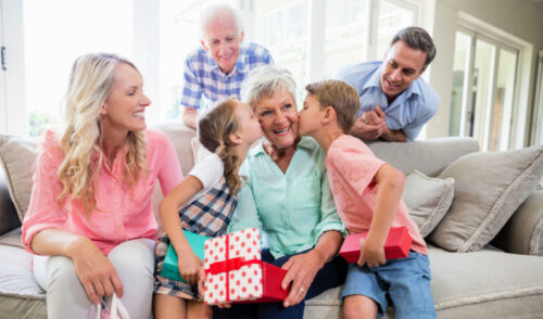 Grandmother receiving gifts from her grandchildren while sitting on an off white couch
