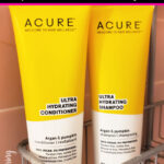 Yellow bottles of Acure Shampoo and Conditioner in a shower rack.