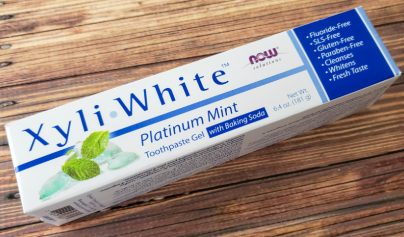Now Solutions Xyli-White Platinum Mint Toothpaste on a wood table.