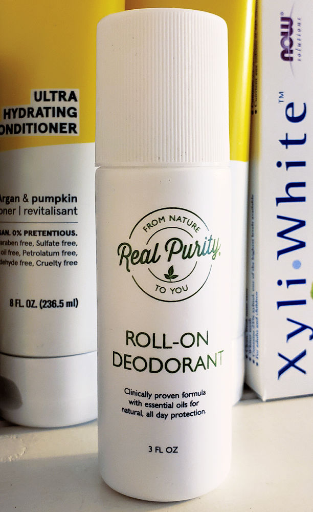 Real Purity Roll-On Deodorant on a table in front of shampoo and conditioner.