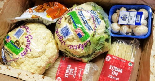 Cauliflower, mushrooms, rice noodles and pretzels in a shipping box.