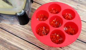 Ham, bell pepper and shallots spread out into the cavities of a red Instant Pot egg bites silicone mold.