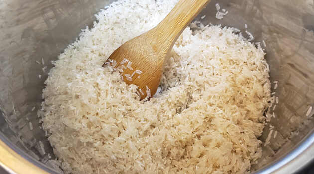 Jasmine rice being sauteed in an Instant Pot with a wooden spoon before being pressure cooked.