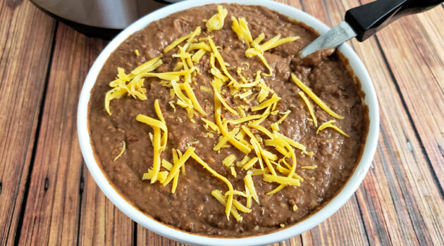 White bowl of homemade refried beans sprinkled with cheese on a wood table in front of an Instant Pot.