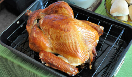Thanksgiving turkey in roasting pan on table with green tablecloth.
