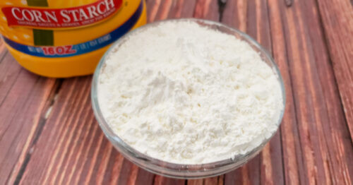 Cornstarch in clear bowl on wood table.