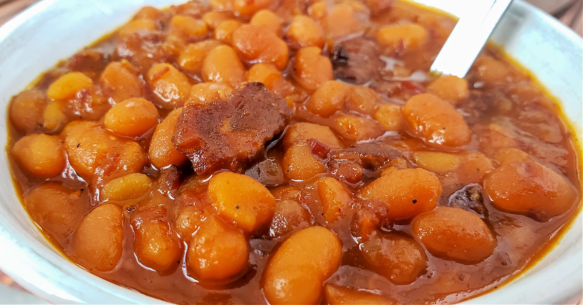 Close up of baked beans that were made in an Instant Pot in a bowl with a spoon.