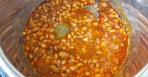 Cooked baked beans in Instant Pot with bay leaf floating in it.