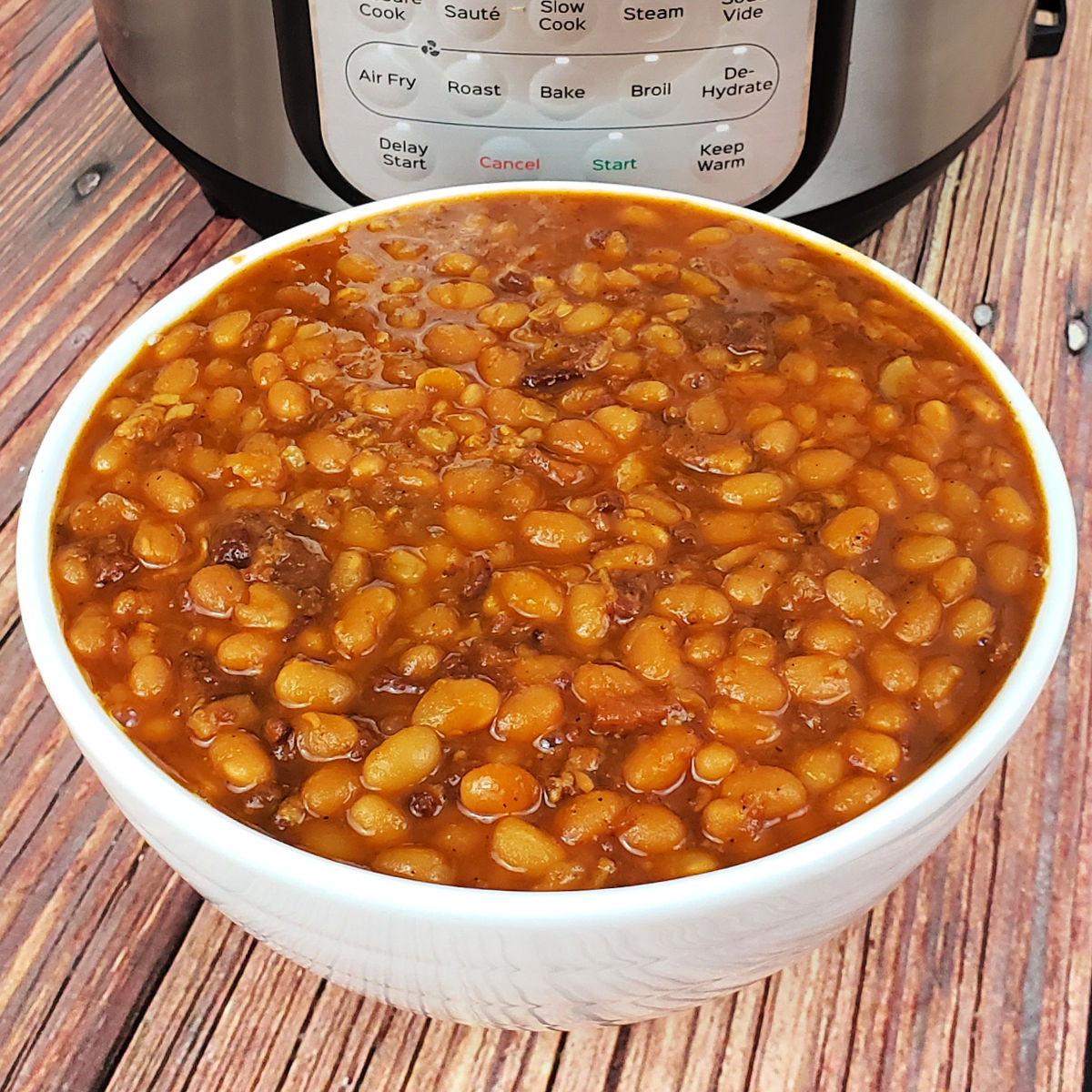 Baked beans in white serving bowl in front of Instant Pot on table.