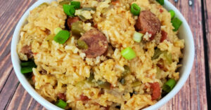 Chicken and sausage jambalaya served in white bowl and garnished with sliced green onions.