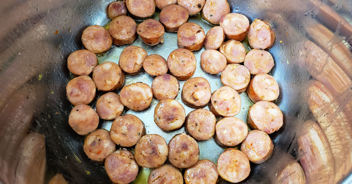 Andouille sausage slices being sautéed in Instant Pot inner pot.