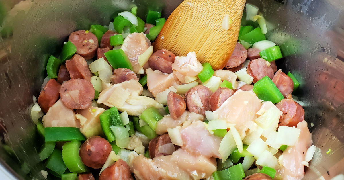 Chopped chicken added to Instant Pot inner pot with Andouille sausage, green bell pepper, celery, onion and garlic.