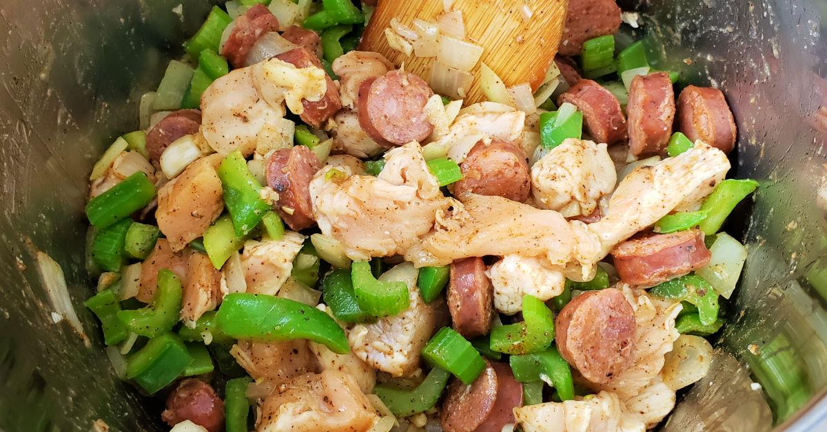 Cajun seasoning being stirred into chicken and sausage jambalaya mixture in Instant Pot inner pan.