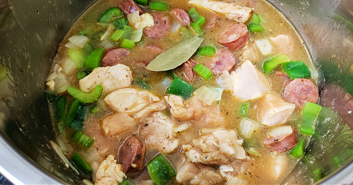 Chicken stock and bay leaf being stirred into the rest of the Instant Pot Jambalaya ingredients before being pressure cooked.