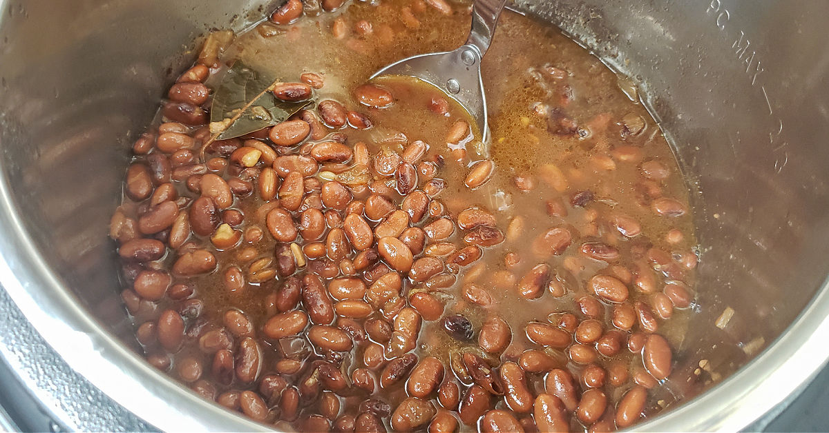 Cooked Pinto beans in Instant Pot being stirred with spoon.