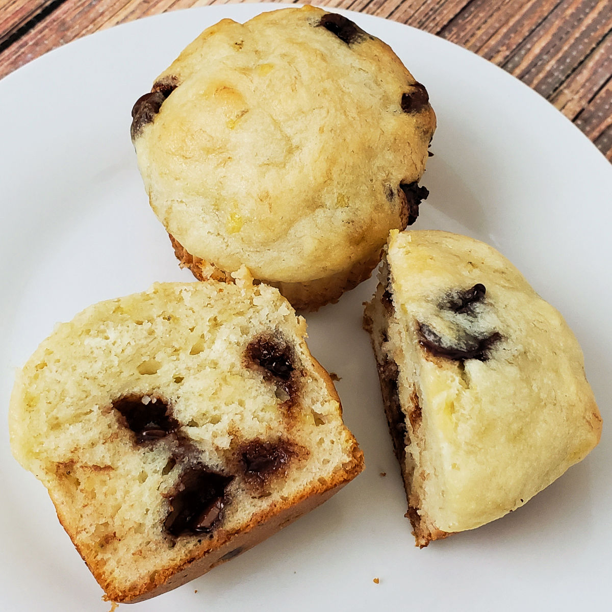 Two gluten free banana muffins on a plate with one cut in half to show melted chocolate chips.